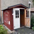 """Auf der Fruchtfolge """"Höfe-Tour"""" gesehene braun-weiß gestrichene Holzhütte auf dem Bauernhof, die Tür steht offen, Schild zeigt """"offen"""""""